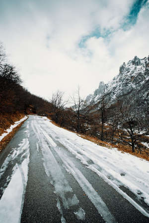 A road on the mountains covered with snow and a mountain range as the background