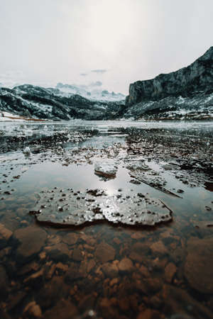 Some frozen water and pieces of ice in a frozen lake in the middle of the mountains during winter
