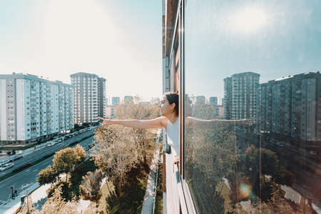 A surprised young woman pointing out something while on a window with the city as the background