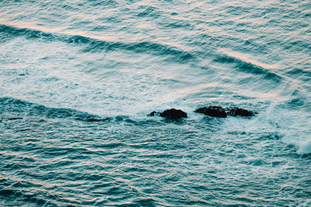 Aerial view of the ocean with the waves and re rocks during a bright day, relaxing scene on blue tones