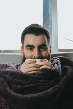 A young man hipster with beard holding a cup of coffee while covered on a blanket in the sofa