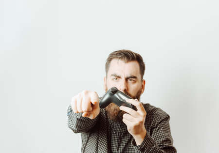 A young hipster man with a white background holding a console pad while angry signaling something out