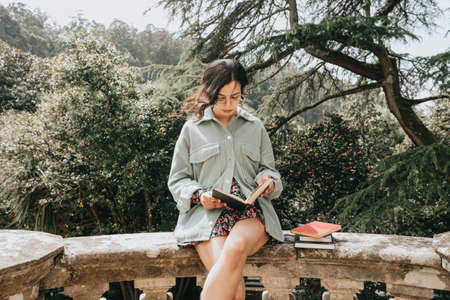Young woman sitting on an old building reading a book during a sunny day with copy space lifestyle and happiness concept