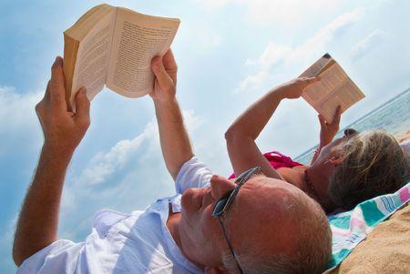 Mature couple reading, relaxing on tropical beach. The sky is blue with clouds in the background.