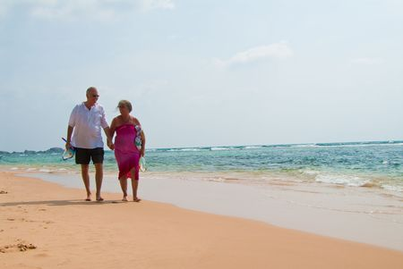 Mature couple walking on tropical beach holding hands, the ocean is turquoise blue. Stock Photo