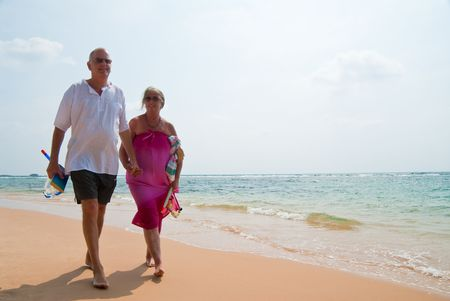 male senior adult: Mature couple walking on tropical beach holding hands, the ocean is turquoise blue. Stock Photo