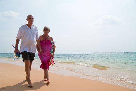 senioren wandelen: Ouder paar lopen inzake tropisch strand holding hands, de zee is turquoise blauw.