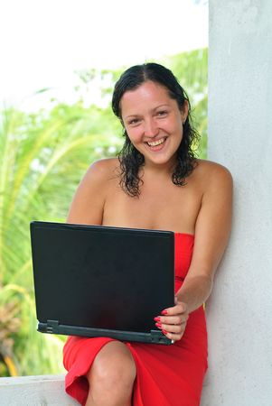 Laughing beautiful young woman in red dress with laptop on knee typing photo
