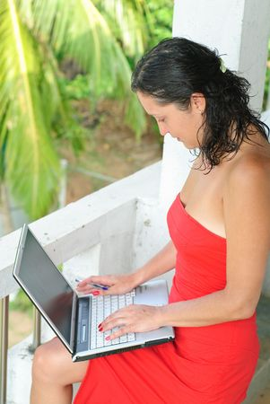 Beautiful young woman in red dress with laptop on knee typing photo