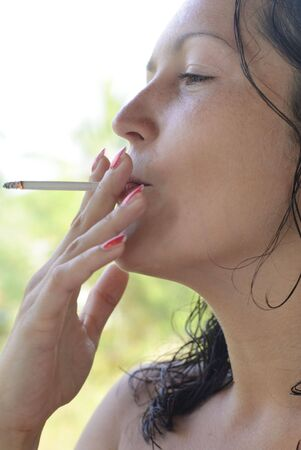 Beautiful young woman smoking cigarette outside. Tropical background with palm trees out of focus. Stock Photo