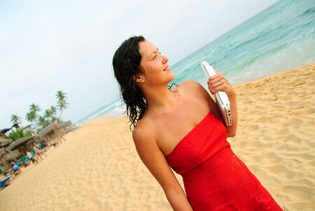 Beautiful young woman walking with laptop on the beach. The sun is setting and light is moody, she�s smiling and content after good days work. photo