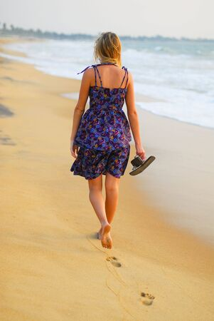 Beautiful young blond girl taking a stroll on the beach with flipflops in hand Stock Photo - 4623093