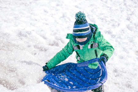 boy haveing fun in a snow during christmas winter holiday on a sleigh. Toddler kid riding a sledge. Children play outdoors in snow. Little boy enjoy a sleigh ride. Child sledding