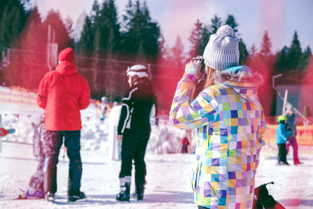 ski resort, a girl looks at the ski mountain on which skiers are going down