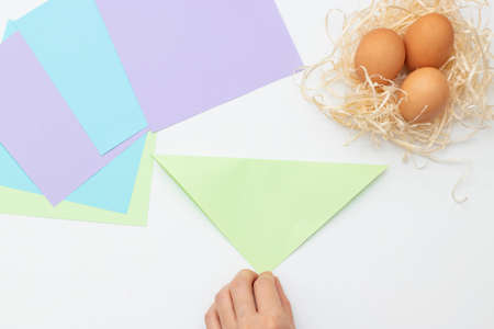 DIY Children's Easter craft bunny with an egg. Step 2. Easter paper step by step instructions. Happy bunny holds egg. Children's Art Project, needlework, crafts for children, springtime