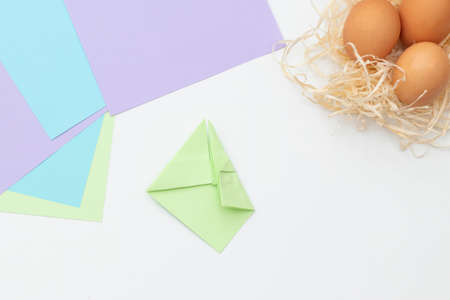 DIY Children's Easter craft bunny with an egg. Step 8. Easter paper step by step instructions. Happy bunny holds egg. Children's Art Project, needlework, crafts for children, springtime