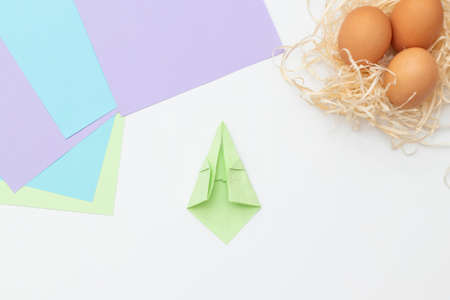 DIY Children's Easter craft bunny with an egg. Step 9. Easter paper step by step instructions. Happy bunny holds egg. Children's Art Project, needlework, crafts for children, springtime
