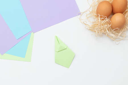 DIY Children's Easter craft bunny with an egg. Step 11. Easter paper step by step instructions. Happy bunny holds egg. Children's Art Project, needlework, crafts for children, springtime