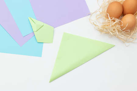 DIY Childrens Easter craft bunny with an egg. Step 14. Easter paper step by step instructions. Happy bunny holds egg. Childrens Art Project, needlework, crafts for children, springtime.