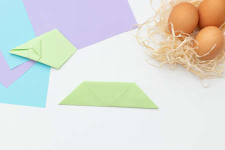DIY Children's Easter craft bunny with an egg. Step 18. Easter paper step by step instructions. Happy bunny holds egg. Children's Art Project, needlework, crafts for children, springtime