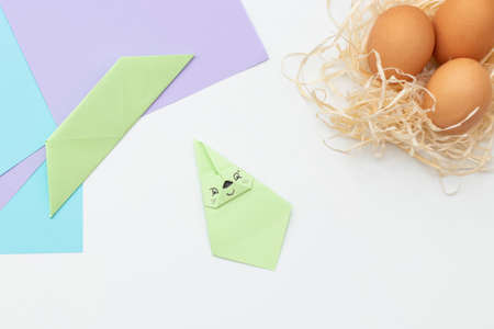 DIY Children's Easter craft bunny with an egg. Step 19. Easter paper step by step instructions. Happy bunny holds egg. Children's Art Project, needlework, crafts for children, springtime