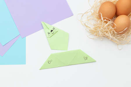 DIY Childrens Easter craft bunny with an egg. Step 20. Easter paper step by step instructions. Happy bunny holds egg. Childrens Art Project, needlework, crafts for children, springtime.