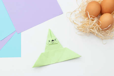 DIY Children's Easter craft bunny with an egg. Step 21. Easter paper step by step instructions. Happy bunny holds egg. Children's Art Project, needlework, crafts for children, springtime