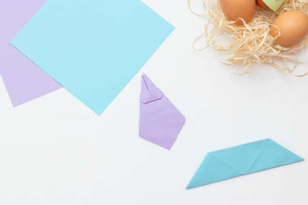 DIY Children's Easter craft bunny with an egg. Step 22. Easter paper step by step instructions. Happy bunny holds egg. Children's Art Project, needlework, crafts for children, springtime