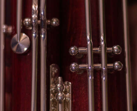 detail of the red wooden bassoon keys to play music in a band