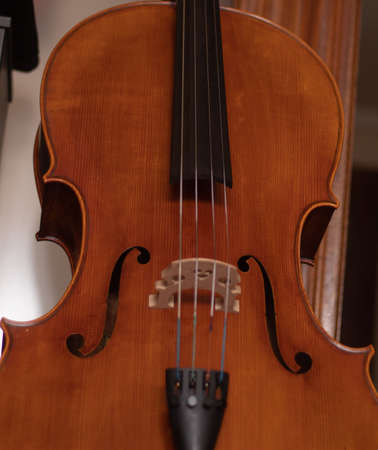 bridge and efe of a brown wooden cello playing music for an orchestra