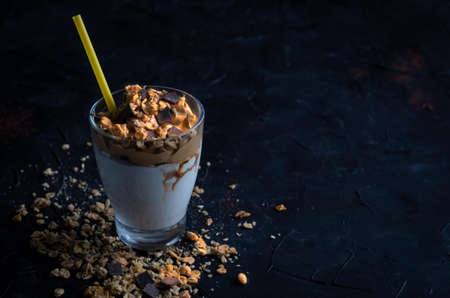 a glass of milk with creamy coffee with cereal muesli and chocolate chips on a dark background with a yellow drinking straw Imagens