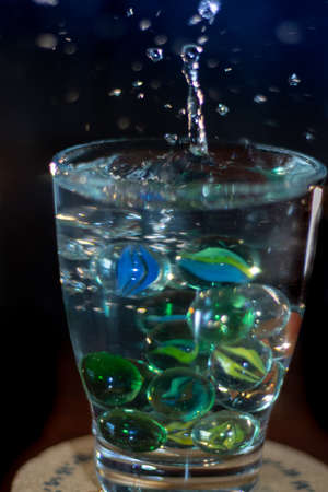 splash of drops in a glass of water and marbles or colors glass balls