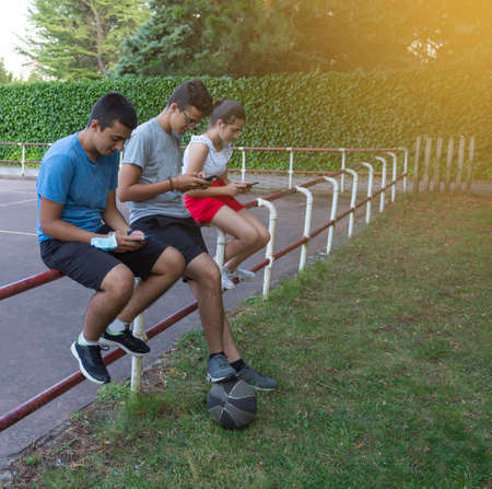 Teenage friends using a smartphone sitting on an outdoor playground fence - Young mobile smartphone addicts - Technology concept with millennials always connected Stockfoto