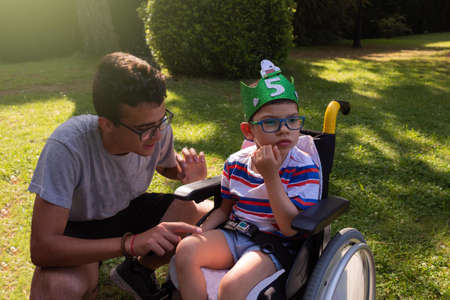 child in wheelchair with Pitthopkins syndrome celebrating his birthday in a garden with a handmade eva rubber wreath and a teenager looking after him Banque d'images