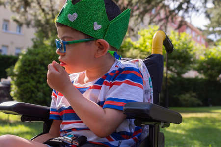 child in wheelchair with Pitthopkins syndrome celebrating his birthday with a handmade wreath Archivio Fotografico