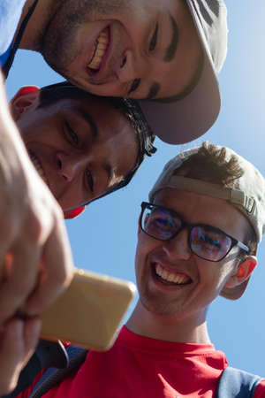 young people smiling looking at photos and mobile social networks during a long walk on the Camino de Santiago in Spain on a summer day Foto de archivo
