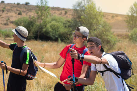 young people with trekking poles doing the Camino de Santiago in Spain and reading the map to orientate themselves and indicating with joy that they have already found the goal of the destination on a summer day