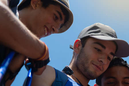 young people smiling, resting and looking at photos and mobile social networks during a long walk on the Camino de Santiago in Spain on a summer day Foto de archivo