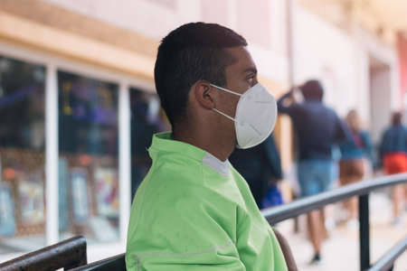 Young teenager wearing a phosphor green sweatshirt and health mask supported by a fence on a rainy day Imagens
