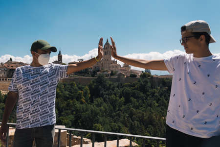 two young men hold with their hands the Cathedral of Segovia in a creative photo from the Alcazar of that town in Spain in a sunny day