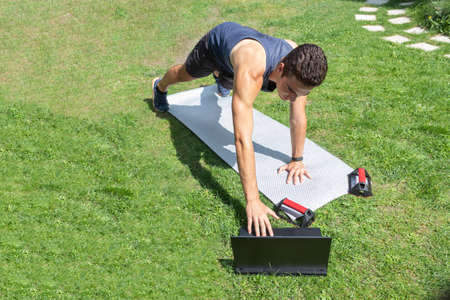 young man handling his laptop and doing push-ups in his backyard in an online session on a sunny day