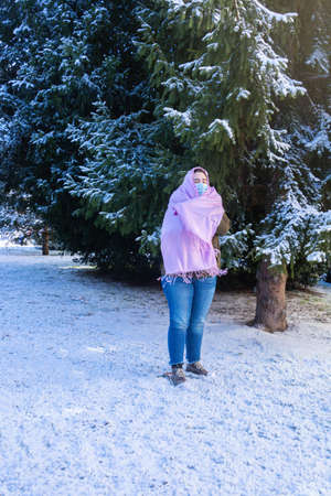 selective focus of a teenage girl wearing a mask and wearing a pink scarf in solidarity with breast cancer disease on a cold winter day surrounded by snow
