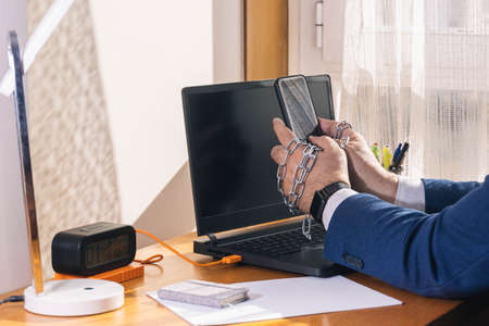 Workaholic entrepreneur's hands locked and chained in mobile addiction during teleworking time