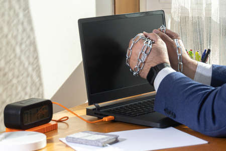 Workaholic entrepreneur's hands trapped in chains spending time doing nothing telecommuting slavery concept
