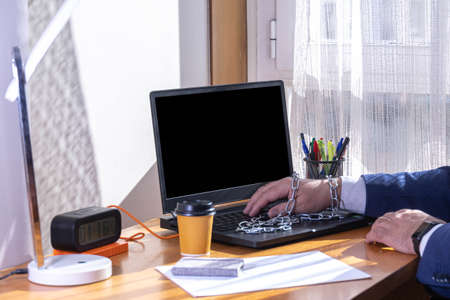 selective focus of a home-based businessman with teleworking and chained to the computer concept of slavery to labor