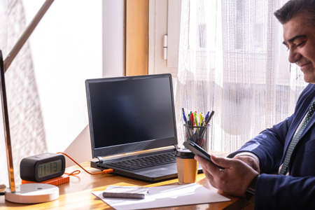 businessman at his desk with laptop and a quick coffee working from home and smiling at what is sent to his mobile phone.