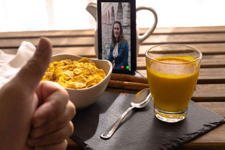 Selective focus of a person making a video call with a girl while having breakfast on a wooden table with cereal and Indian golden milk with curcuma and cinnamon.