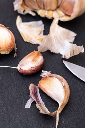cloves of garlic on a black slate board with a knife ready for cutting