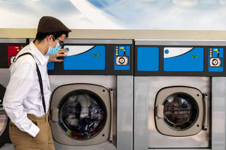 teenager with mask and cap observing how industrial washing machines work to wash the clothes he has brought from home for personal hygiene