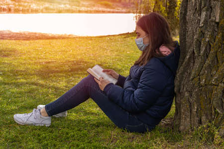 Young girl with a mask sitting in the grass under a sturdy tree with a book in her hands to read and forget about this time of and pandemic. Imagens